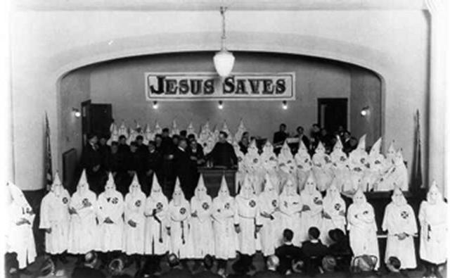 "Photo of a Church gathering of the KKK, meeting underneath a sign that reads, ""Jesus Saves."""