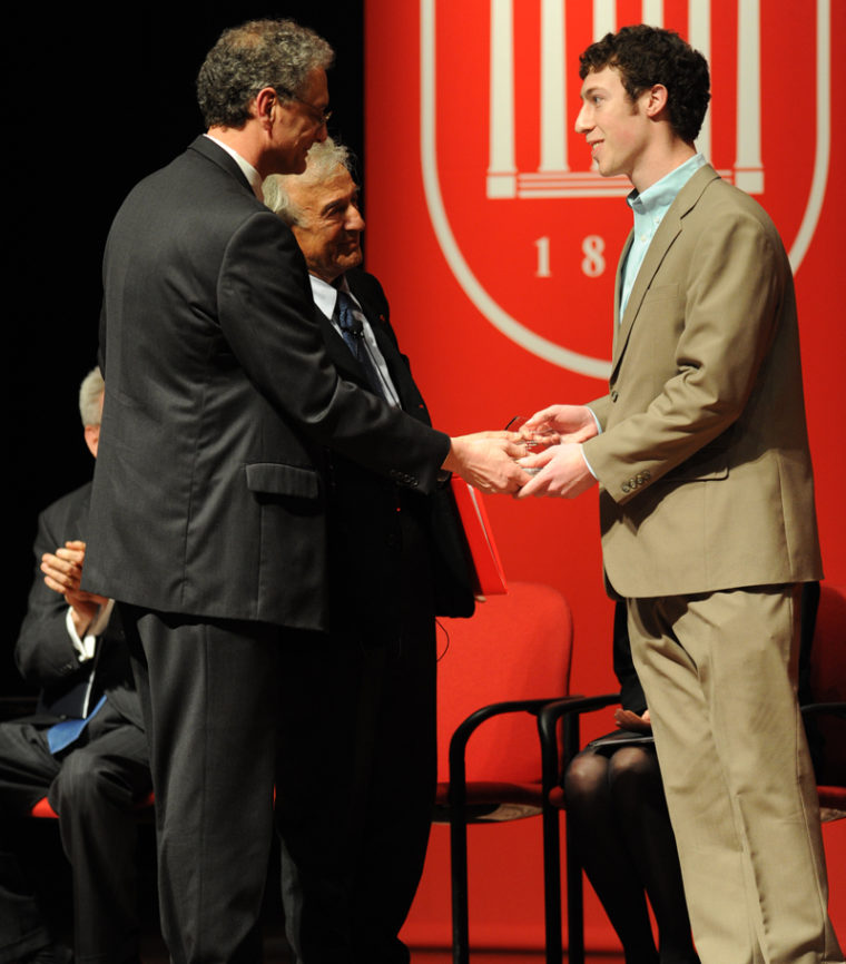 Photo of Taylor McGraw being congratulated by Dean Doug Sullivan-Gonzalez and Nobel Laureate Elie Wiesel, 2010.