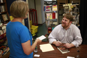 Photo of Weber signing a book for Mrs. Gray in Oxford, MS.