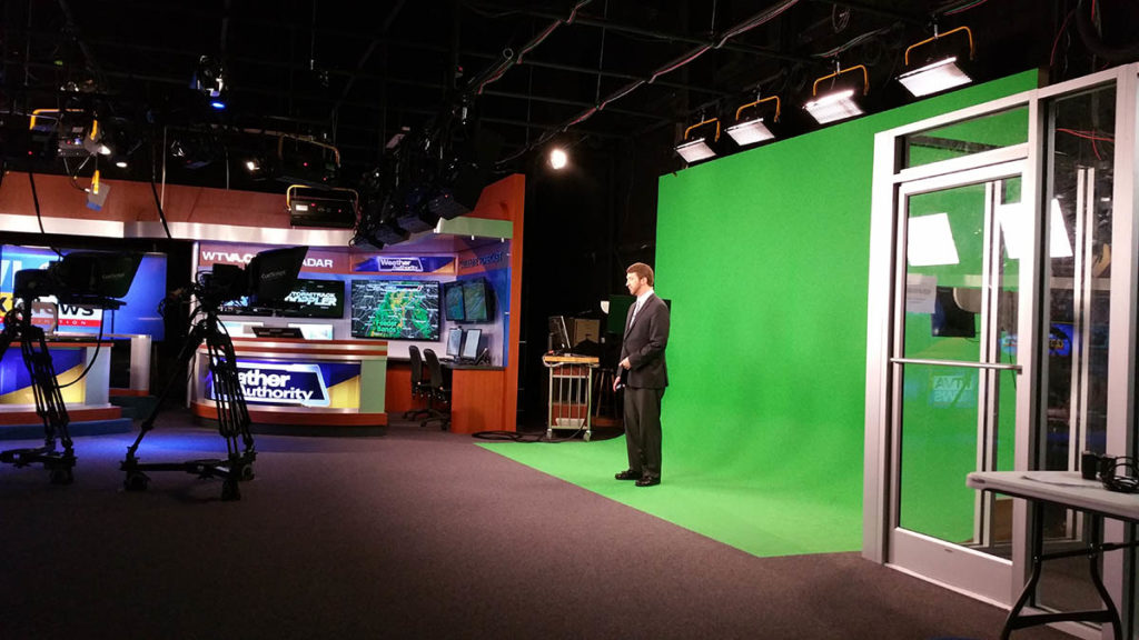 Photo of the weatherman in front of a green screen in Tupelo, MS's WLOV TV studio.