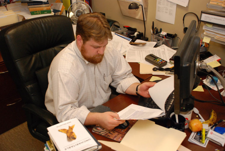 A photo of me reading at my desk in 2010, before I came to need glasses.