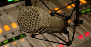 Photo of a microphone and a soundboard.