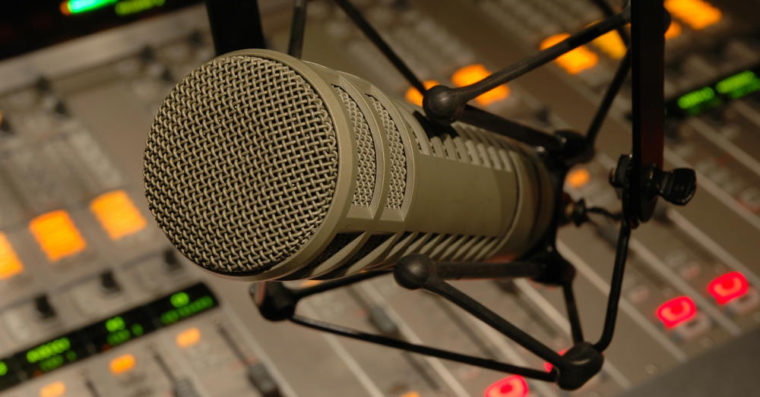 Photo of a microphone in front of a soundboard.