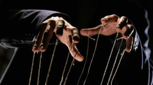 Puppet master's hands and strings.