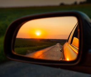 View of a sunset through a rear view mirror.