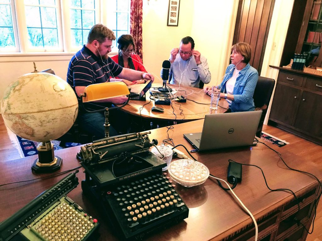 This is a photo of four people sitting around a table and a microphone to record an episode of Philosophy Bakes Bread in May of 2017, in a lovely room near South Gull Lake in Michigan.